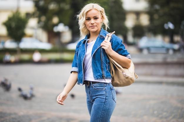 Junge blonde mädchenfrau auf straßenwegquadrat-fontain, gekleidet in blue jeans suite mit tasche auf ihrer schulter im sonnigen tag