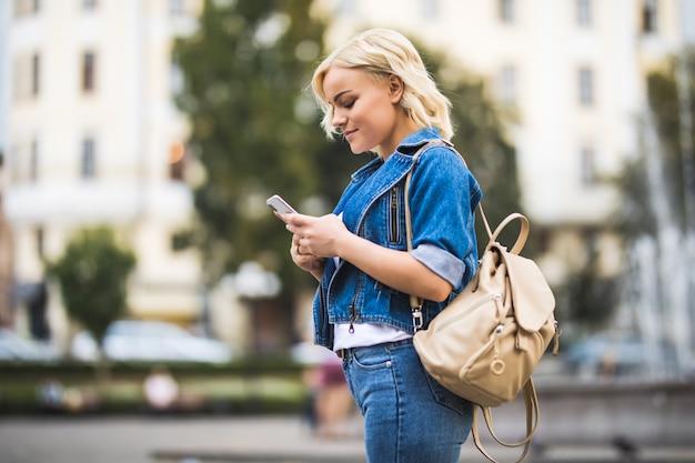 Junge blonde mädchenfrau mit telefon in den händen auf straßenwegquadrat-fontain, gekleidet in blue jeans suite mit tasche auf ihrer schulter im sonnigen tag