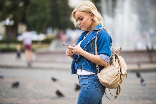 Junge blonde mädchenfrau mit telefon in ihren händen auf straßenwegquadrat-fontain, gekleidet in blue jeans suite mit tasche auf ihrer schulter in sonnigem tag
