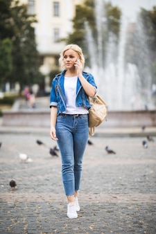 Junge blonde mädchenfrau spricht telefon auf straßenwegquadrat-fontain, gekleidet in blue jeans suite mit tasche auf ihrer schulter in sonnigem tag