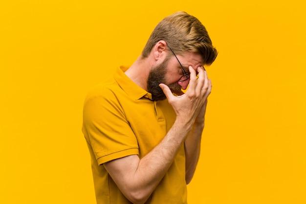 Junge blonde mannbedeckung mustert mit den händen mit einem traurigen, frustrierten blick der verzweiflung und schreit, seitenansicht gegen orange wand