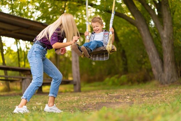 Junge blonde mutter schüttelt ihren kleinen sohn auf einer schaukel in einem grünen park. glückliche kindheit.