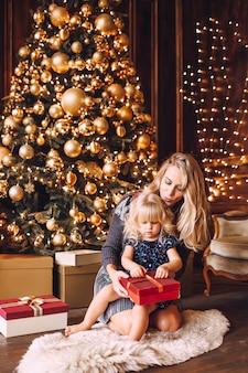 Junge blonde mutter und ihre kleine tochter in der glänzenden kleidung, die ein weihnachtsgeschenk öffnet