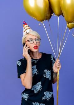 Junge blonde partyfrau, die brille und geburtstagskappe hält, die ballons hält, die seite betrachten, die am telefon lokalisiert auf lila wand spricht
