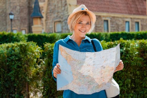 Junge blonde reisende frau mit hut und sonnenbrille mit einer karte der sehenswürdigkeiten eines anderen landes. sommerurlaub und aktive erholung freiheit und aktives lifestyle-konzept
