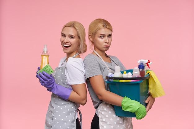 Junge blonde reizende hausfrauen, die gummihandschuhe tragen, während sie sich auf den frühjahrsputz vorbereiten
