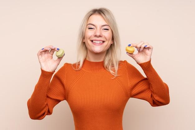 Junge blonde russische frau, die bunte französische macarons hält
