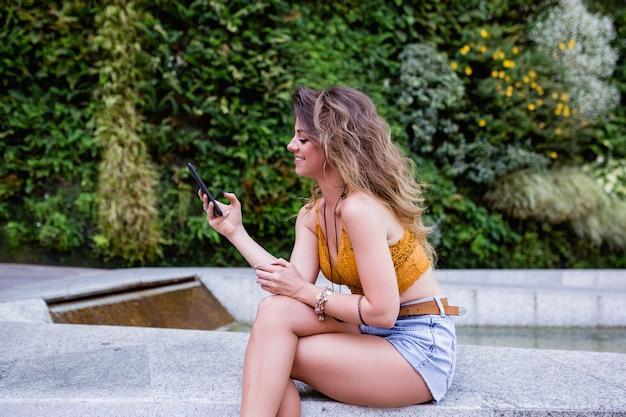 Junge blonde schönheit an der straße unter verwendung des handys und des lächelns. sommerzeit, grüner hintergrund