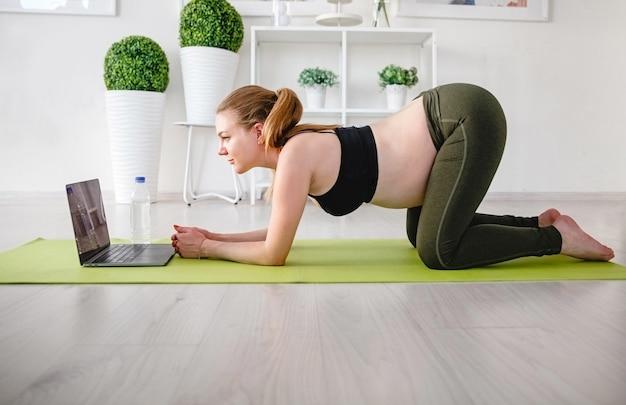 Junge blonde schwangere frau, die sport zu hause auf der matte mit laptop tut