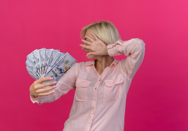 Junge blonde slawische frau, die geld in richtung kamera ausstreckt und gesicht hinter hand lokalisiert auf rosa hintergrund mit kopienraum versteckt