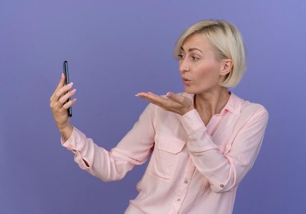 Junge blonde slawische frau, die handy hält und schlagkuss an ihm lokalisiert auf lila hintergrund sendet