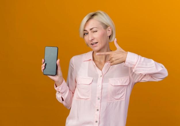 Junge blonde slawische frau hält und zeigt auf telefon