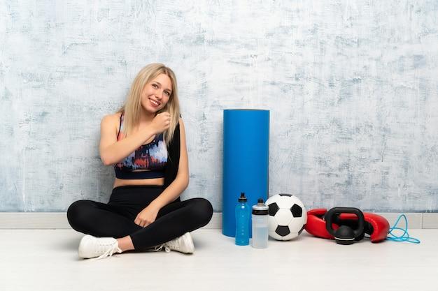 Junge blonde sportfrau, die auf dem boden feiert einen sieg sitzt
