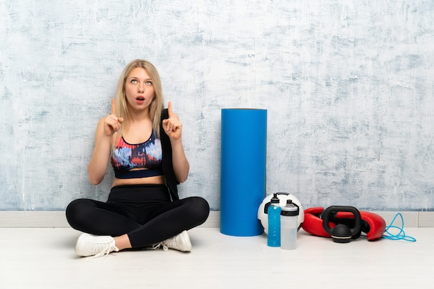 Junge blonde sportfrau, die auf dem boden zeigt mit dem zeigefinger eine großartige idee sitzt