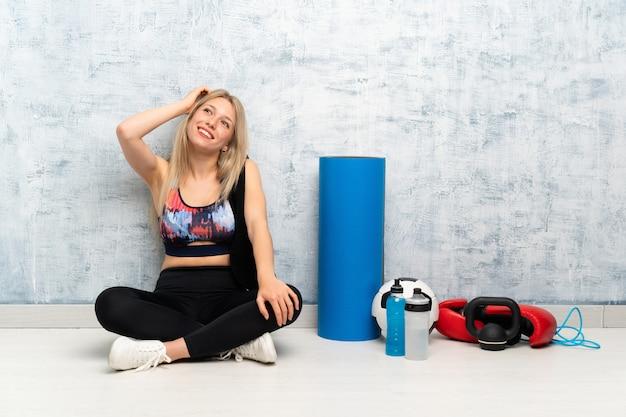 Junge blonde sportfrau, die auf dem bodenlachen sitzt