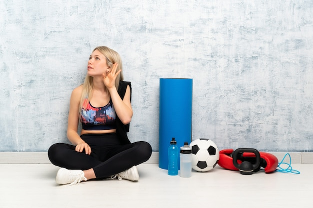 Junge blonde sportfrau, die auf dem hörenden boden etwas sitzt