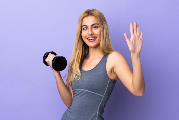 Junge blonde sportfrau, die gewichtheben über isoliertem lila salutieren mit hand mit glücklichem ausdruck macht