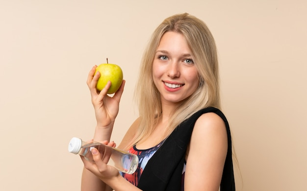 Junge blonde sportfrau mit einem apfel und einer flasche wasser