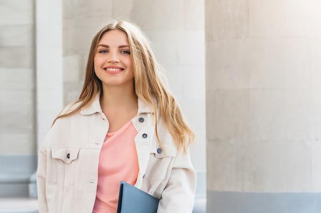 Junge blonde studentin, die gegen universität lächelt.