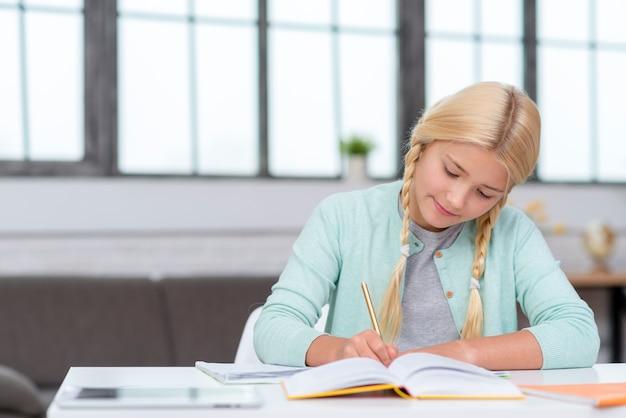 Junge blonde studentin, die notizen von der lektion macht