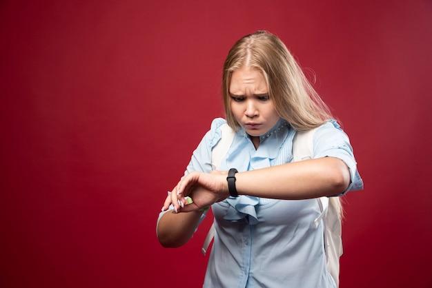 Junge blonde studentin geht zurück zur schule, überprüft die zeit und wird gestresst, weil sie zu spät kommt.