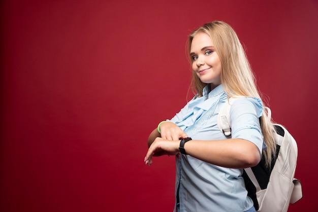 Junge blonde studentin geht zurück zur schule und schaut auf ihre uhr.