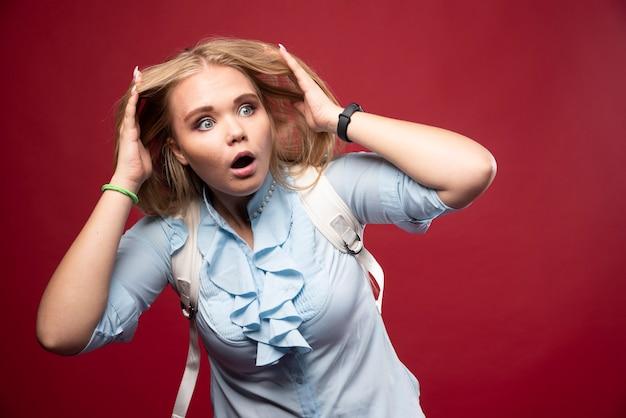 Junge blonde studentin geht zurück zur schule und sieht deprimiert und nervös aus.