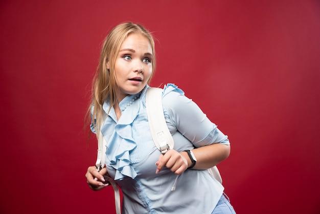 Junge blonde studentin mit ihrem rucksack geht zurück zur schule und fühlt sich schön und glücklich.