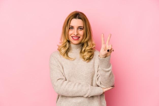 Junge blonde süße frau, die einen isolierten pullover trägt, der nummer zwei mit den fingern zeigt.