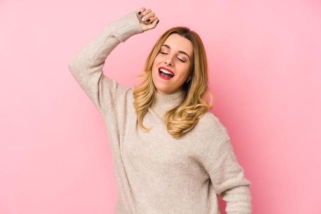 Junge blonde süße frau, die einen pullover isoliert trägt, der einen besonderen tag feiert, springt und arme mit energie hebt.
