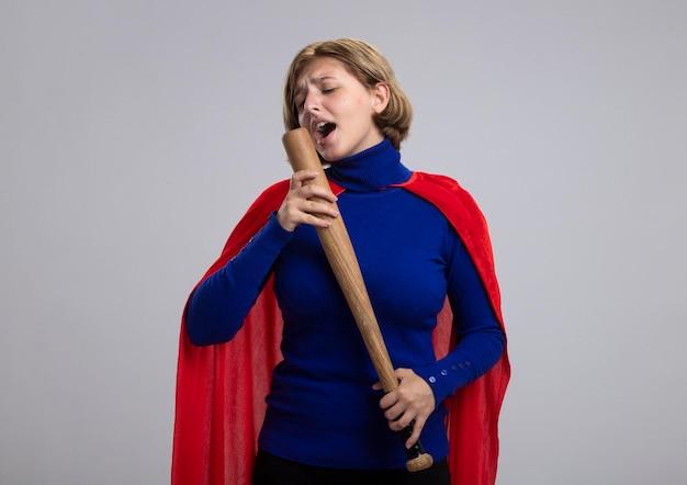 Junge blonde superheldenfrau im roten umhang, der baseballschläger hält und betrachtet, der es als mikrofon verwendet, das auf weißer wand mit kopienraum lokalisiert wird