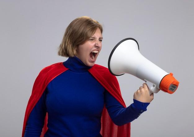 Junge blonde superheldenfrau im roten umhang, der lautsprecher hält und betrachtet, der es lokalisiert auf weißer wand schreit