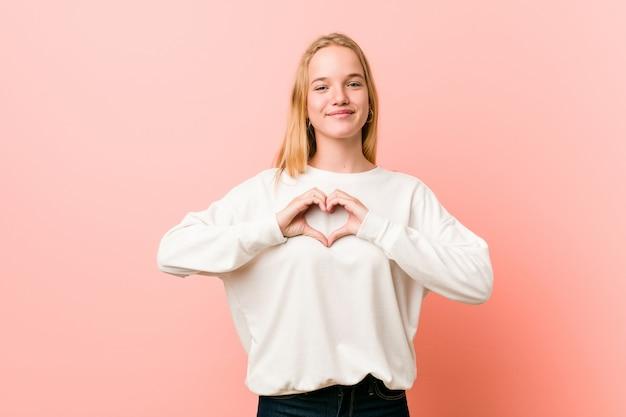 Junge blonde teenagerfrau, die lächelt und eine herzform mit händen zeigt.