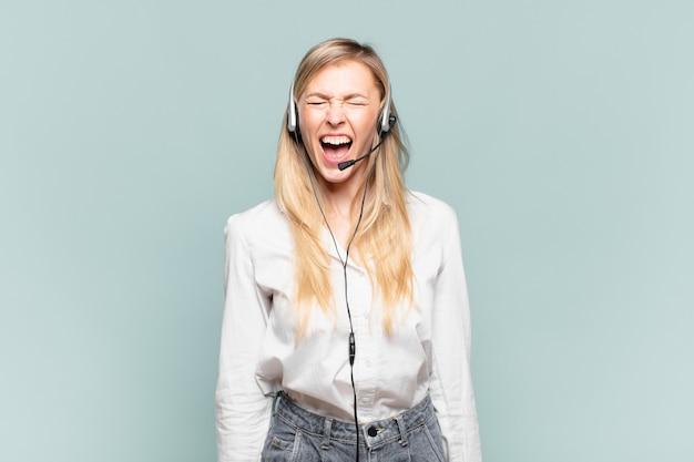 Junge blonde telefonverkäuferin, die aggressiv schreit, sehr wütend, frustriert, empört oder verärgert aussieht und nein schreit