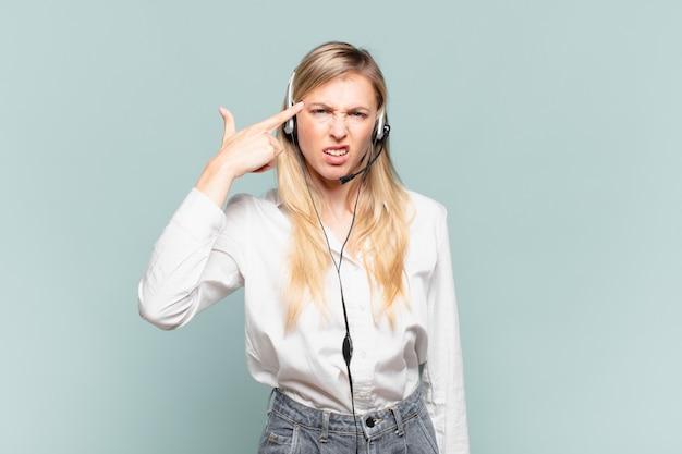 Junge blonde telefonverkäuferin, die sich verwirrt und verwirrt fühlt und zeigt, dass sie verrückt, verrückt oder verrückt sind
