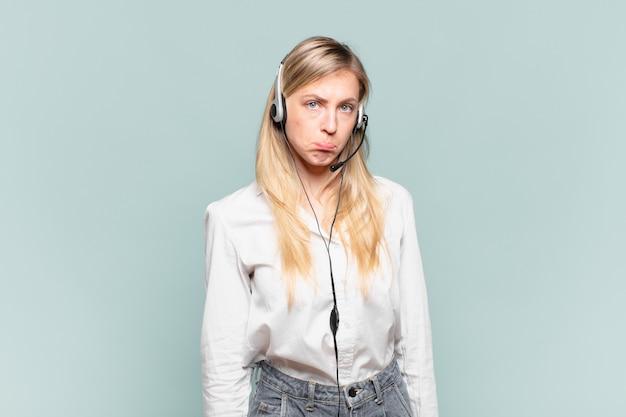 Junge blonde telefonverkäuferin, die traurig und weinerlich mit einem unglücklichen blick ist und mit einer negativen und frustrierten einstellung weint