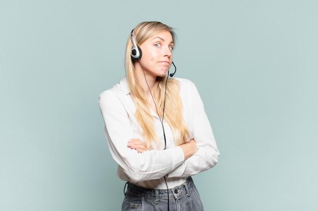 Junge blonde telefonverkäuferin zuckt mit den schultern, fühlt sich verwirrt und unsicher, zweifelt mit verschränkten armen und verwirrtem blick