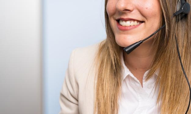 Junge blonde telemarketerfrau über lokalisierter blauer wand und dem lächeln