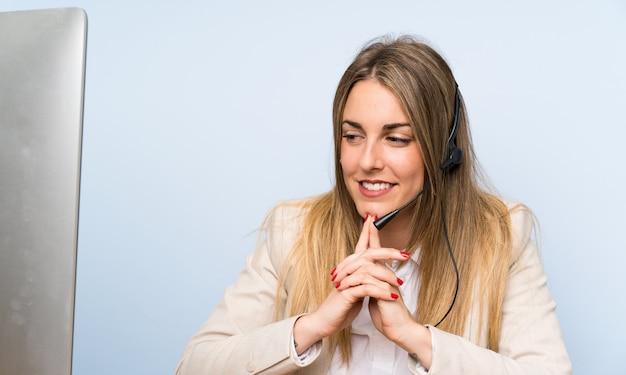 Junge blonde telemarketerfrau über lokalisierter blauer wand