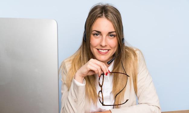 Junge blonde telemarketerfrau und -c $ lächeln