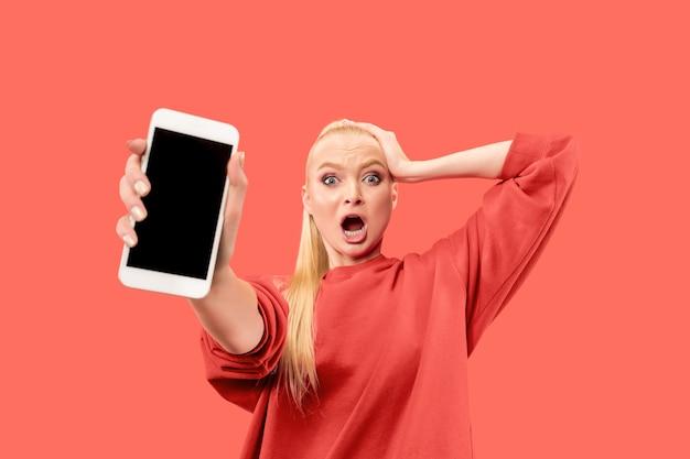Junge blonde überraschte frau, die auf korallenhintergrund mit smartphone schreit