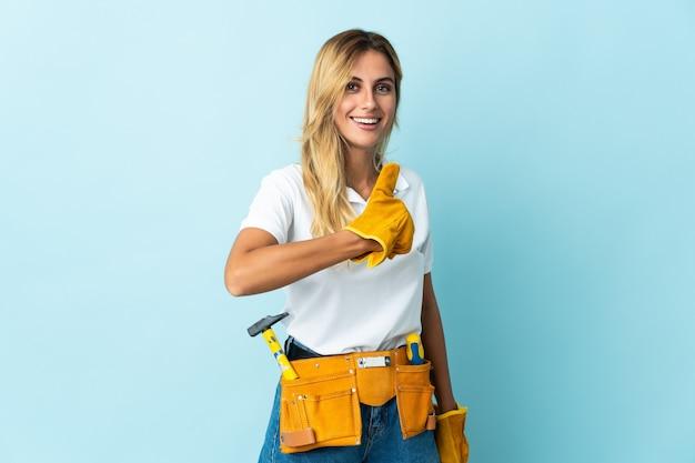 Junge blonde uruguayische elektrikerin blau, die eine daumen hoch geste gibt