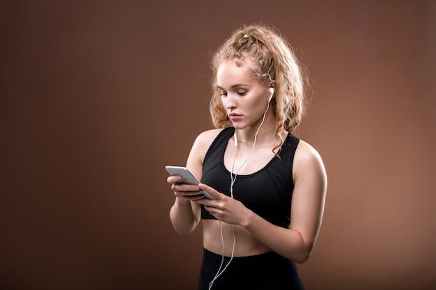 Junge blonde weibliche millennial im schwarzen trainingsanzug und in den kopfhörern, die durch die wiedergabeliste im smartphone scrollen, während sie etwas auswählen, um zu hören