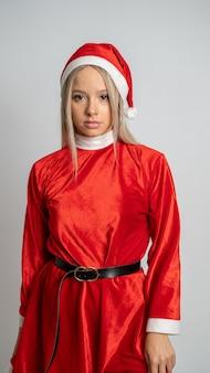 Junge blondhaarige frau, die in einem fräulein santa claus kostüm auf grauer wand aufwirft