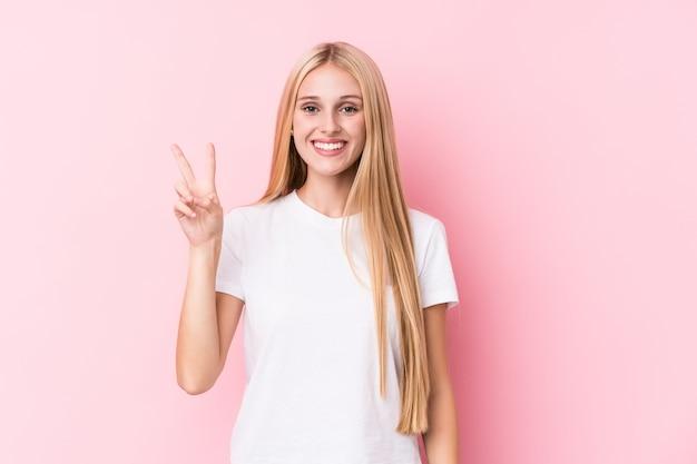 Junge blondine auf dem rosa, das siegeszeichen zeigt und breit lächelt.