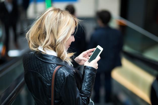 Junge blondine, die ihren smartphone auf einer rolltreppe in der u-bahn verwenden