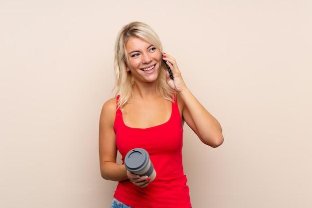 Junge blondine, die kaffee halten, um und ein mobile wegzunehmen