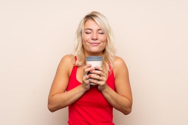 Junge blondine, die kaffee halten, um wegzunehmen