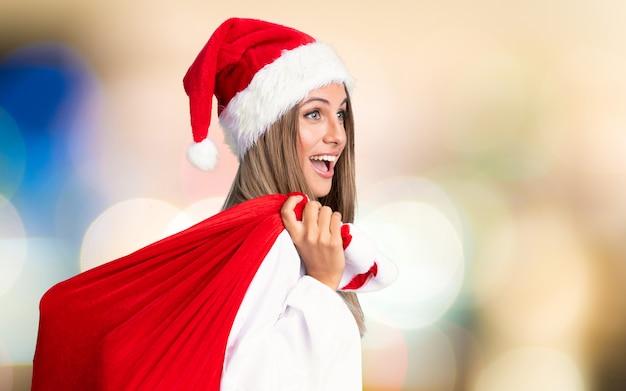 Junge blondine, die voll eine tasche von geschenken in weihnachtsfeiertage auf unfocused hintergrund aufheben