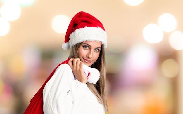 Junge blondine, die voll eine tasche von geschenken in weihnachtsfeiertage auf unfocused wand aufheben